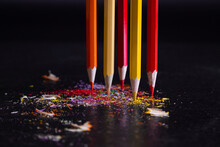 Five Sharpened Crayons In The Warm Colors Of The Spectrum Stand Upright Against A Dark Background In Multicolor Shavings Of Pencil Leads. Shallow Depth Of Field. Focused On Yellow