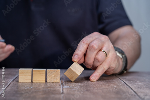 Fototapety, obrazy: A mock up of Four blank timber block cubes three in a block with a man holding the end cube forming a multi faceted diamond shape