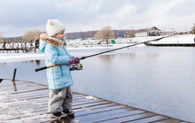Winter, Spring Fishing On Paid Snow Covered Ice Pond, Lake In Country Club. Little Girl Catching Fish With Spinner. Fisherman With Spinning Rods. Hobby, Entertainment, Competition.Cold Frozen Weather