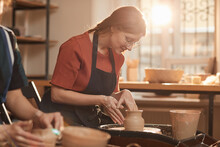 Warm Toned Portrait Of Young Woman Shaping Clay On Pottery Wheel In Sunlit Workshop And Enjoying Arts And Crafts, Copy Space