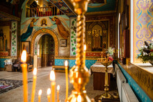 Interior Of An Orthodox Ukrainian Church. Burning Candles On A Gilded Candlestick Or Candelabra. Temple Entrance