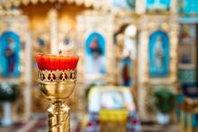 Interior Of An Orthodox Ukrainian Church. Interior Of An Orthodox Ukrainian Church. Burning Red Candle On A Gilded Candlestick Or Candelabra.