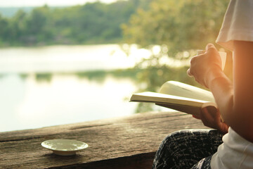 Midsection Of Woman Reading Book Against Lake