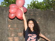 Portrait Of Cheerful Girl Holding Red Helium Balloons Against Wall