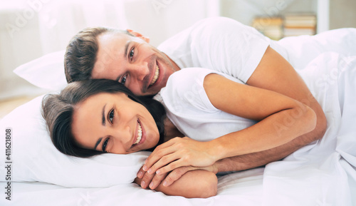 Fototapeta Happy cute young beautiful couple in love hugging each other and having fun in the big white bed after dream obraz