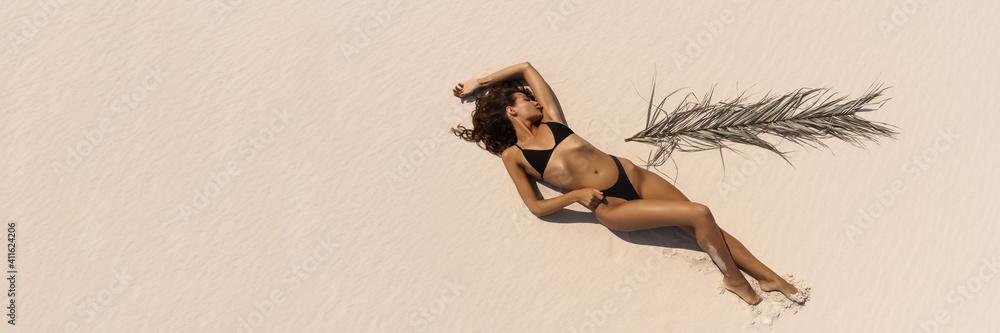 Fototapeta Top Aerial Drone View of Woman in Swimsuit Bikini Relaxing and Sunbathing on Beach