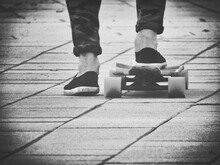 Low Section Of Man With Skateboard On Footpath