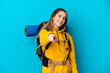 canvas print picture - Young mountaineer woman with a big backpack isolated on blue background pointing front with happy expression
