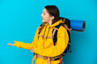 canvas print picture - Young mountaineer woman with a big backpack isolated on blue background with surprise expression while looking side