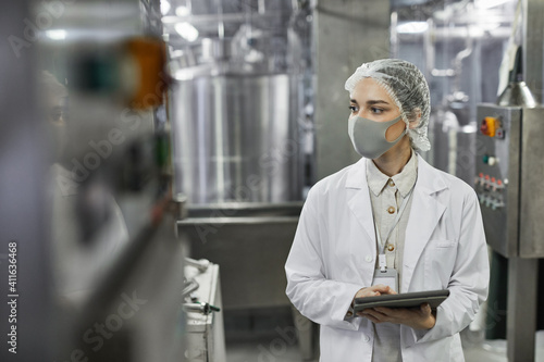 Waist up portrait of young woman wearing mask and holding digital tablet during quality control inspection at food factory, copy space