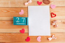 February 27. Blue Cube Calendar With Month And Date And White Mockup Blank On Wooden Background.