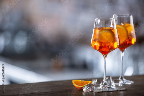 Typical summer sekt drink aperol spritz served in wine glass with aperol, prosecco, soda and a slice of orange © weyo