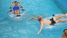 Tourists On The Float Flowing In The Lazy River At A Water Park On A Summer Day.