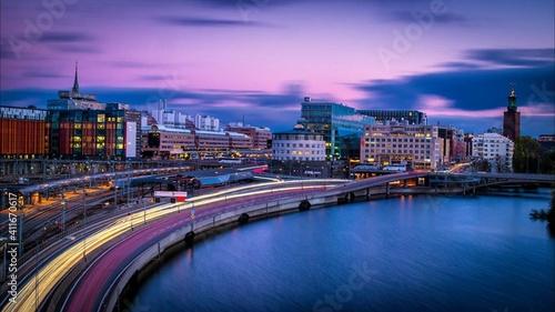 Obraz na płótnie Light Trails On Street By Buildings Against Sky At Night