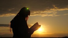 A Woman Reads Book In Rays Of The Sun. Girl Turns Pages Of Book In Rays Of Sunset, She Reads Bible Outdoors. Studying The Word Of God At Sunrise On Top Of Mountain. Searching For Truth In Scriptures