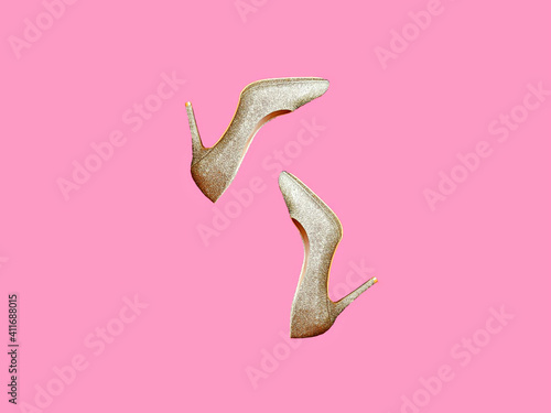 Pair of golden sparkling shoes on bright pink background