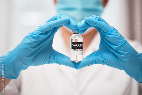Doctor's hand in sterile medical gloves showing heart shape with vaccine COVID-1 Fototapeta
