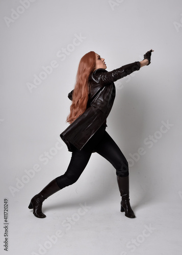 full length portrait of girl with long red hair wearing dark leather coat, corset and boots Fototapet