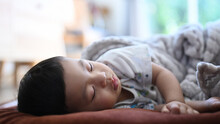 Close Up View Of Peaceful Baby Sleeping On Bed In A Bright Room.