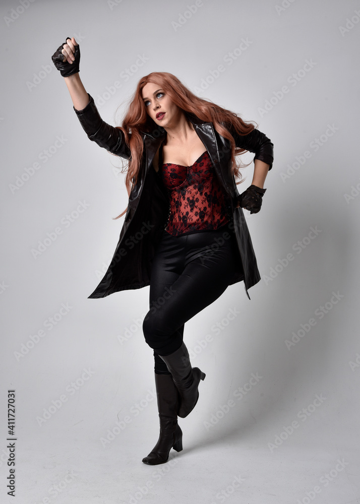 Fotografie, Obraz full length portrait of girl with long red hair wearing dark leather coat, corset and boots