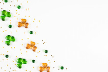 Shamrock Symbols Made Of Green And Orange Glass Hearts Lying On White Background With Sparse Gold Stars Confetti. Happy St. Patrick's Day Irish Holiday Card 17 March Lucky Clover. Flat Lay, Copy Space