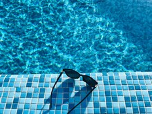 High Angle View Of Sunglasses At Poolside
