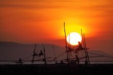Silhouette Fishermen On Beach Against Sky During Sunset