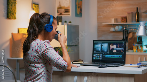 Woman video editor with headset working with footage and sound sitting in home kitchen Wallpaper Mural