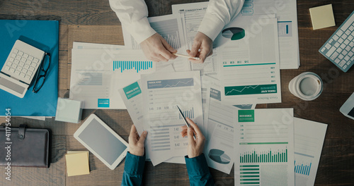 Business people checking financial charts together
