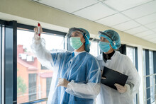 Couple Nurse Wearing Medical Protective Clothes Holding Blood Samples In Test Tube