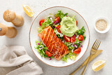 Grilled salmon fish fillet and fresh green lettuce vegetable tomato salad with avocado guacamole. Top view