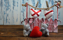 Small Soft Toys Of Bears With A Heart On A Wooden Floor Against The Background Of An Out-of-focus Red Fence With Metal Hearts On It