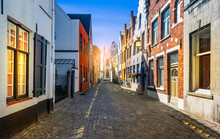 Narrow Cobblestone Street With Traditional Houses In Medieval City Center Of Bruges, Belgium.