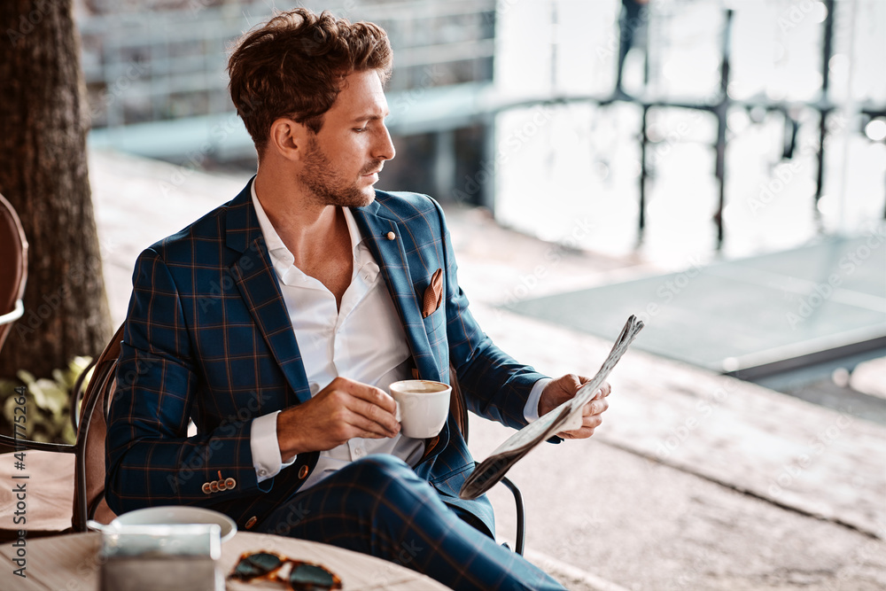 Fototapeta Handsome man drinking coffee and reading newspaper in cafe