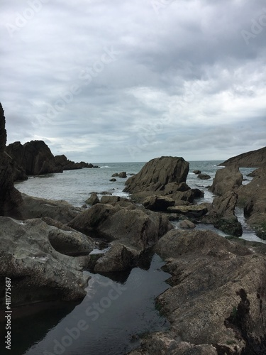 Fototapeta Rocks On Sea Shore Against Sky obraz