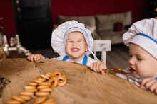 Little Cute Cook With Cutlery Sitting On A Kitchen, Twin Brothers, Tangerine, Bagels