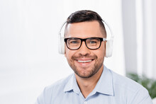 Happy Businessman In Glasses And Wireless Headphones Smiling While Looking At Camera