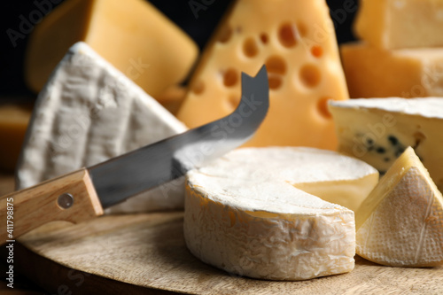 Different sorts of cheese and knife on wooden board, closeup Wallpaper Mural
