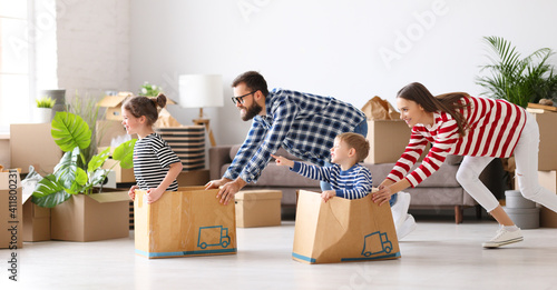 Optimistic family having fun during relocation in new flat #411800231