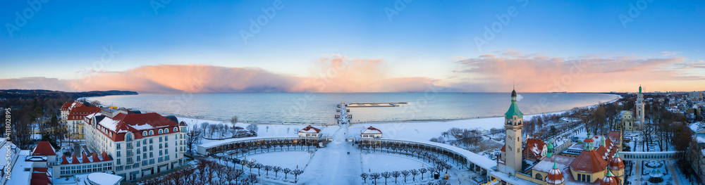 Fototapeta Beautiful sunset over the snowy beach and pier (Molo) in Sopot at winter. Poland
