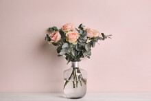Vase With Bouquet Of Beautiful Roses On White Wooden Table Near Beige Wall