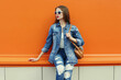 Leinwandbild Motiv Portrait of smiling young woman wearing a denim jacket and jeans with backpack on a orange background