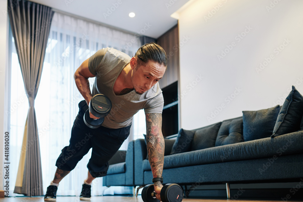 Fototapeta Serious fit mixed-race man doing dumbbells plank row exercise lifting dumbbell weights in his apartment