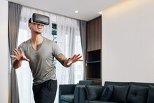 Excited Young Man In Virtual Reality Headset Playing Video Game At Home, Trying To Entertain Himself At Home