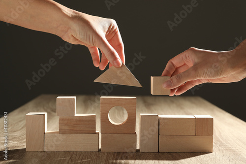 Canvas Print People constructing with wooden building blocks, closeup