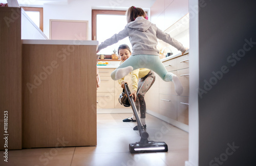 Obraz Two small girls sisters indoors at home, having fun when hoovering. - fototapety do salonu
