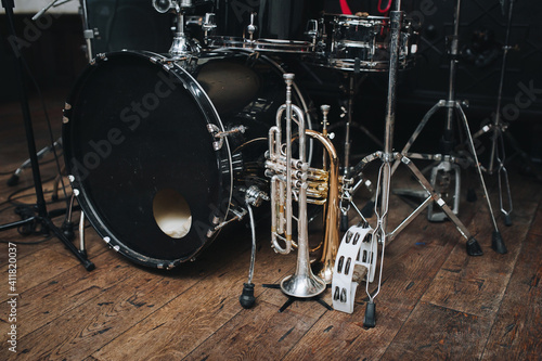 Fotografija A black vintage drum kit and a microphone stand are on stage and next to them are two trumpets (alto and bass) and a white tambourine