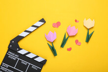 Clapperboard, Origami Tulips And Hearts On A Yellow Background. Filmmaking Concept. Valentine's Day. Top View