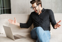 Excited Unshaven Man Gesturing While Taking Video Call On Laptop