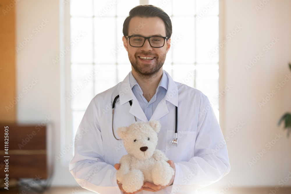 Fototapeta Portrait of smiling young Caucasian male pediatrician in white medical uniform hold fluffy teddy bear toy show care and good service in children hospital. Happy man doctor work in kids private clinic.